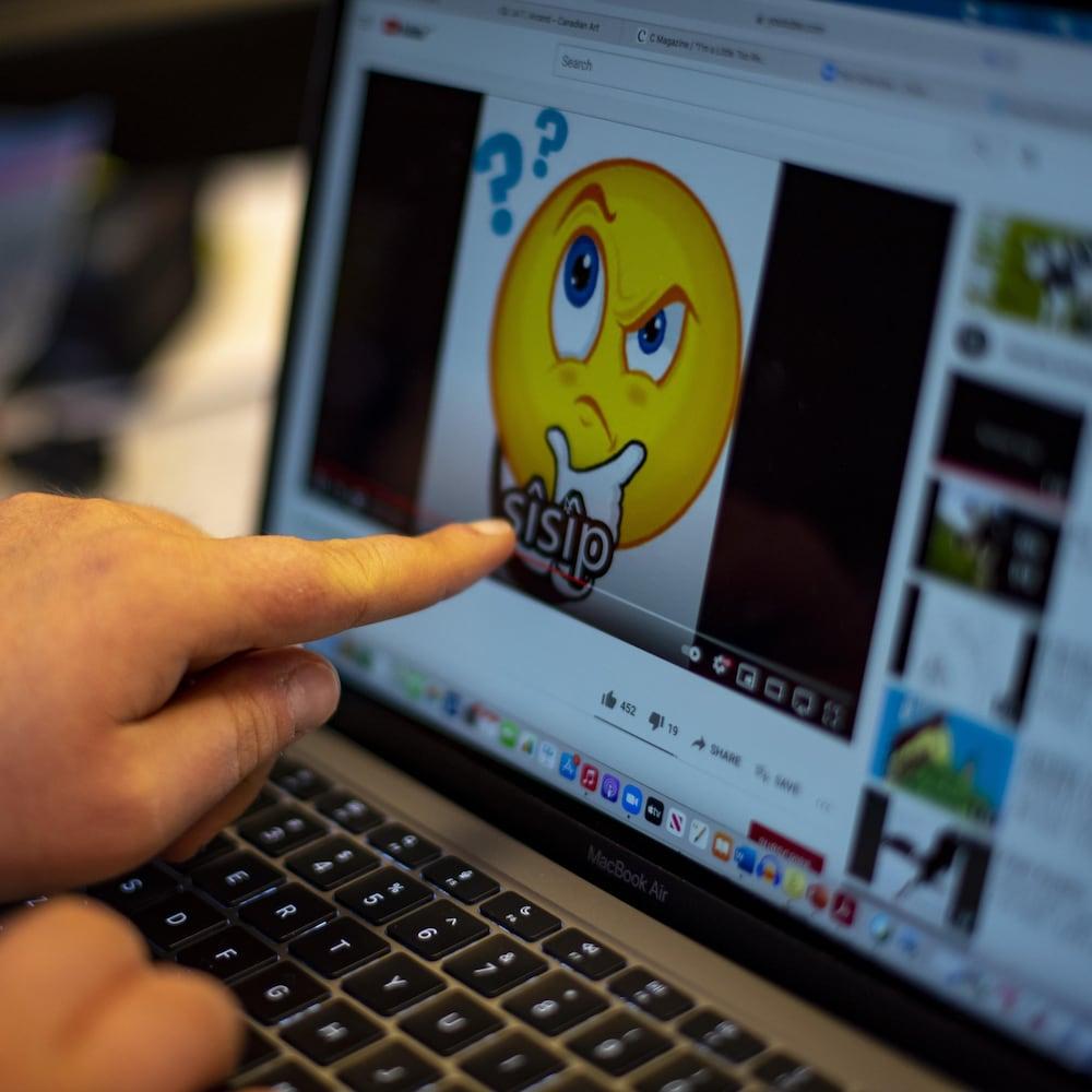 Cameron Adams montre du doigt son écran d'ordinateur, sur lequel se trouve une vidéo pour apprendre le cri.