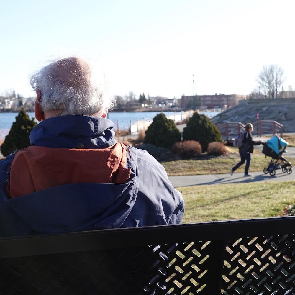 Pierre Vincelette, de dos, est assis sur un banc et il regarde vers le lac.