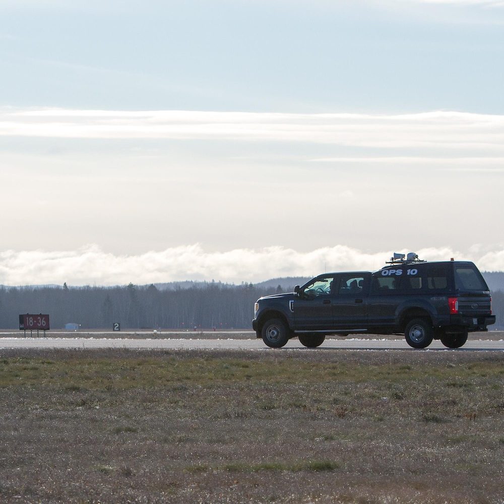 Une camionnette circule sur une piste de l'aéroport.