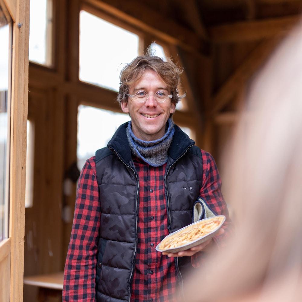 Fred Pellerin ouvre la porte, une tarte à la main.