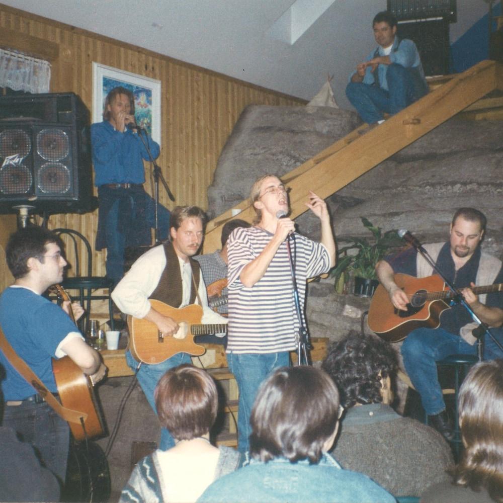 Fred Pellerin chante, entouré de musiciens.