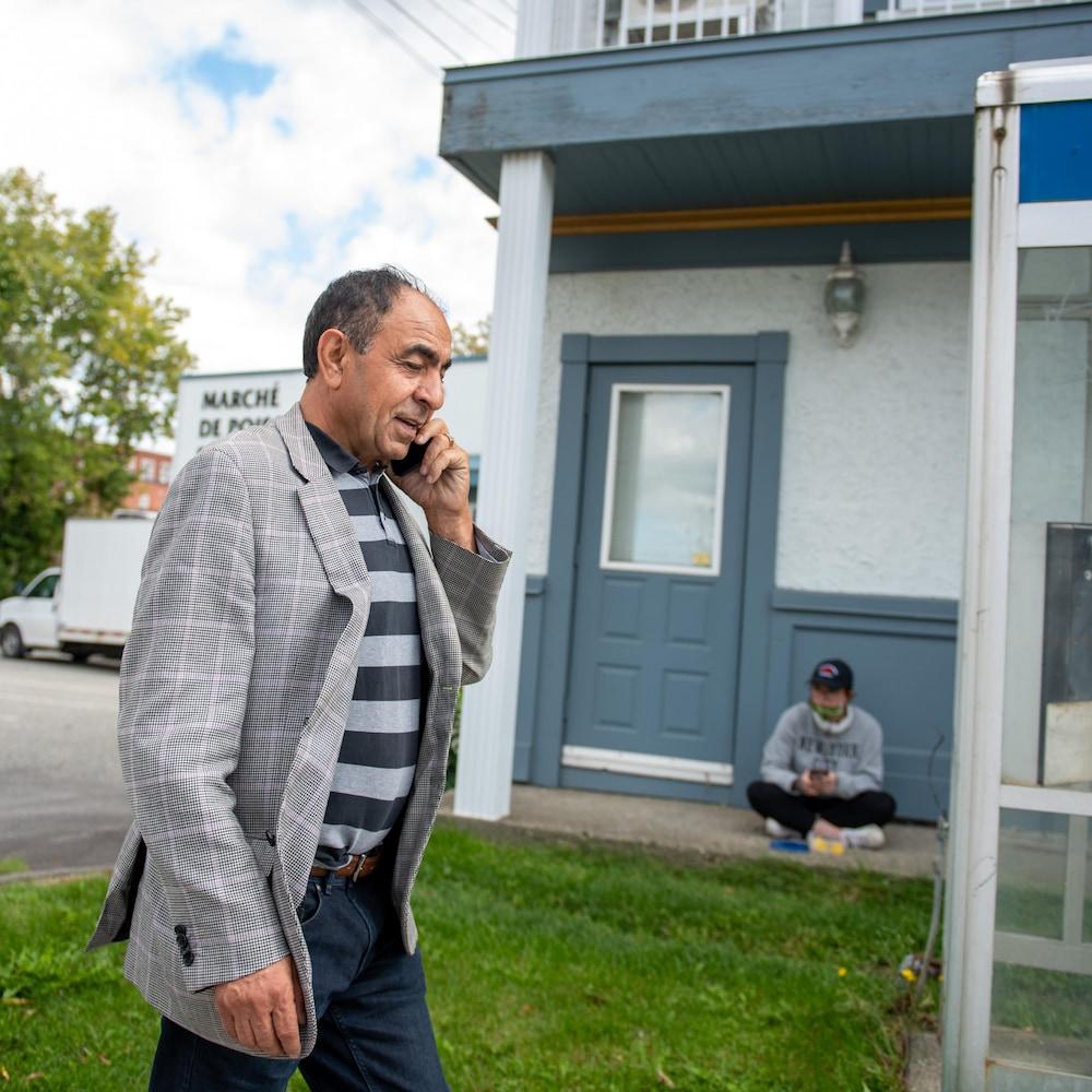 M. Habibi qui marche dans la rue en parlant au téléphone.