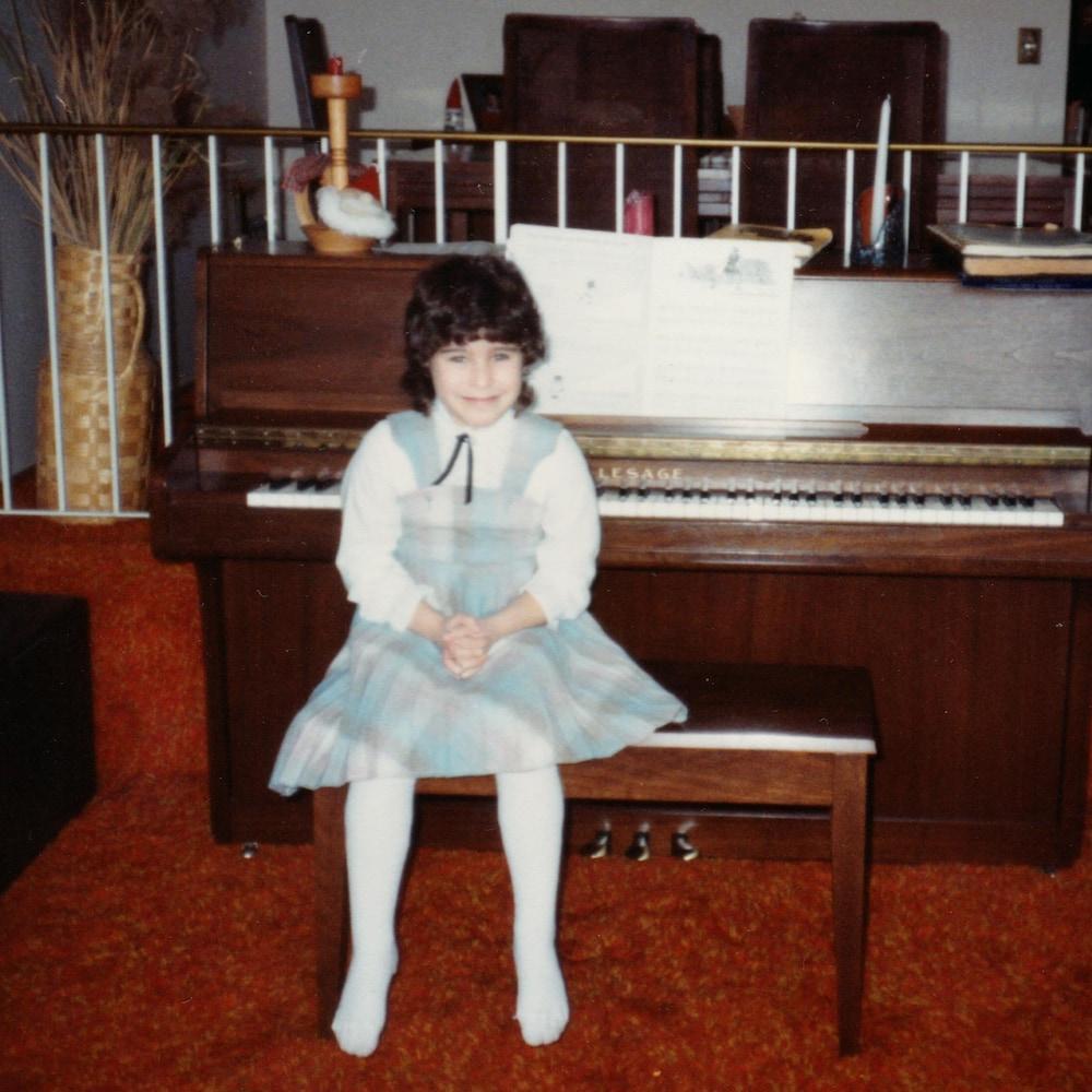Joëlle, enfant, portant une robe dans un salon, à côté d'un piano.