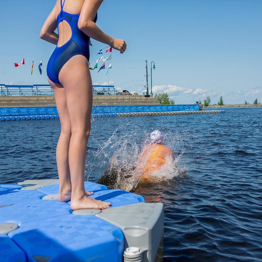 Alexandra, sur le quai, regarde Alexann sauter à l'eau.