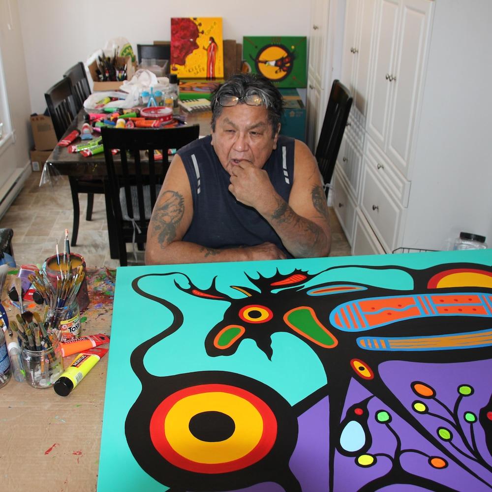 Frank Polson réfléchit, assis devant une toile.