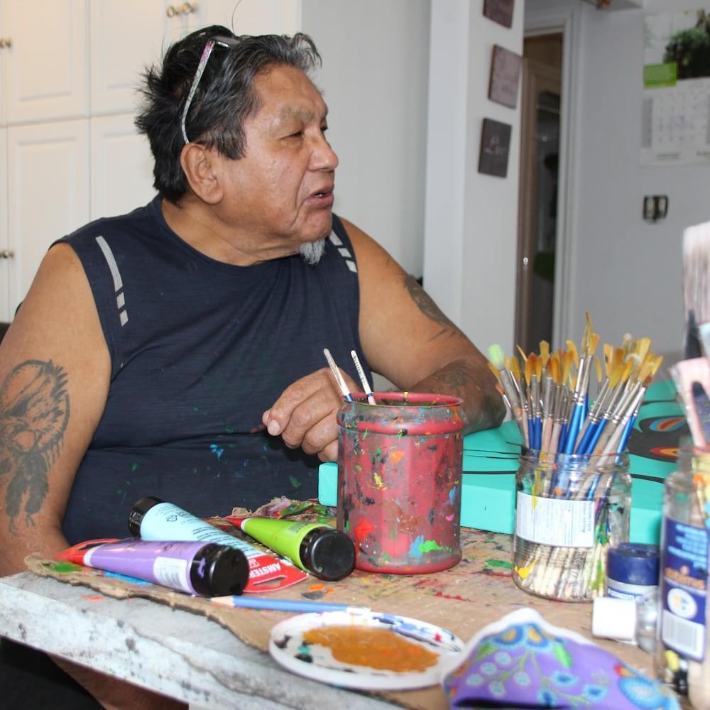 Frank Polson est assis à sa table de travail, entouré de pinceaux et de tubes de peinture.