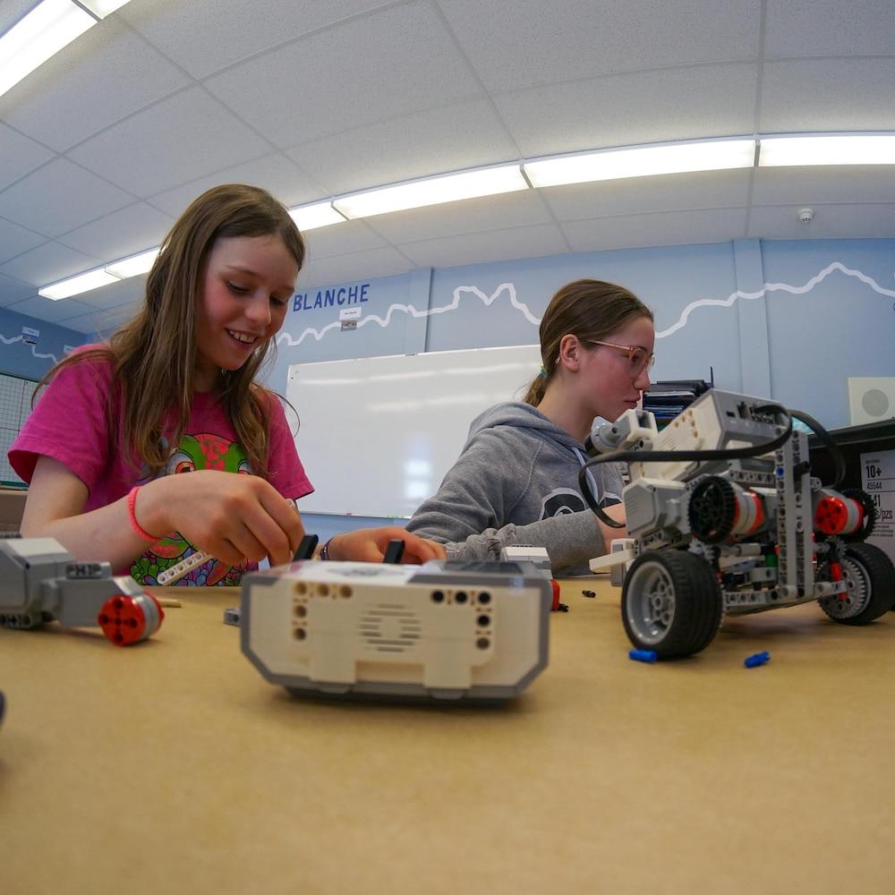 Deux jeunes filles fabriquent un robot.
