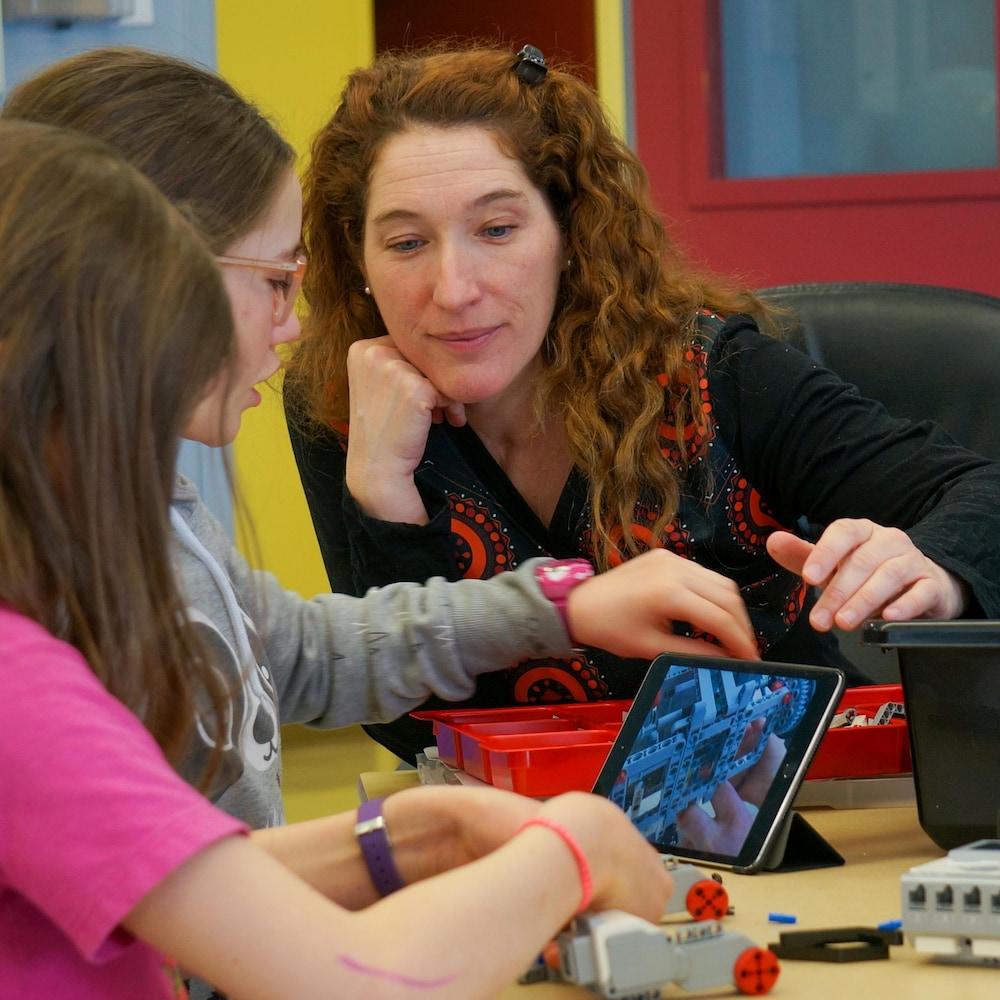 Karine Dubé aide deux élèves à fabriquer un robot.