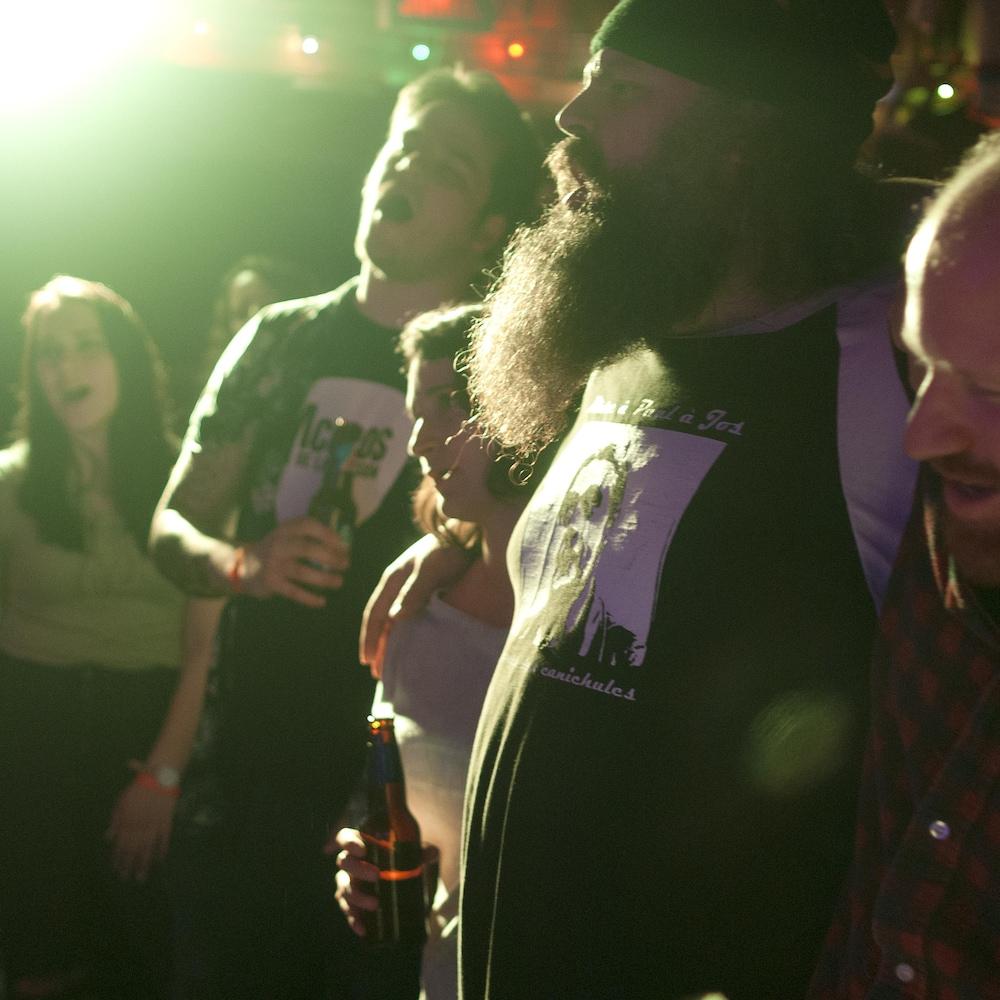 Une petite foule chante, lors d'un spectacle, bras-dessus bras-dessous.