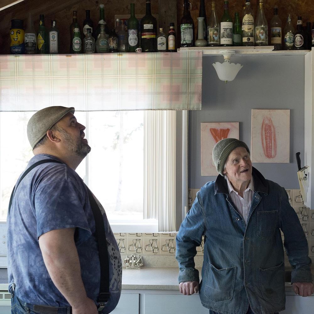 Un homme et son père debouts dans une cuisine regardent le plafond.