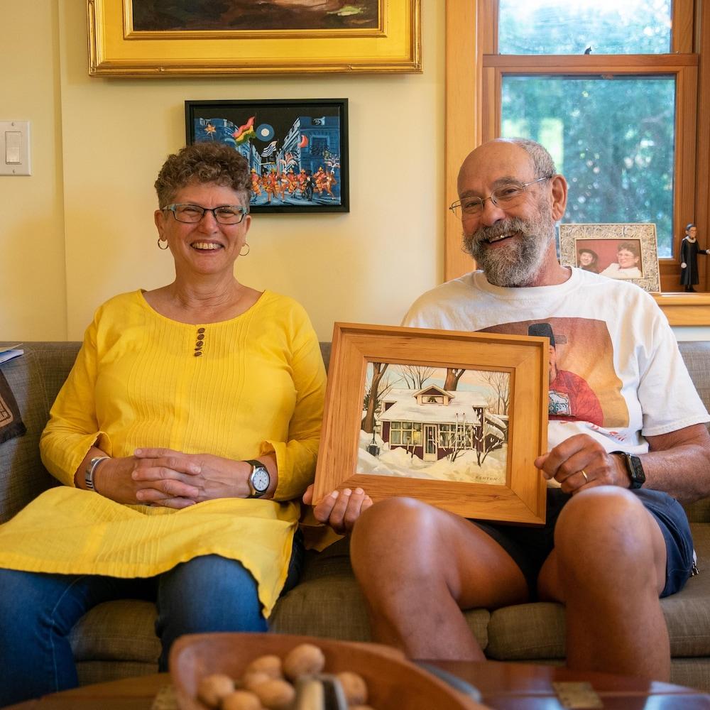 Daina et Barry avec le portrait de leur maison avant les rénovations.
