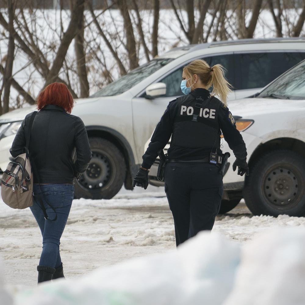 La policière Érika Landry marche près d'une dame qui a demandé de l'aide.