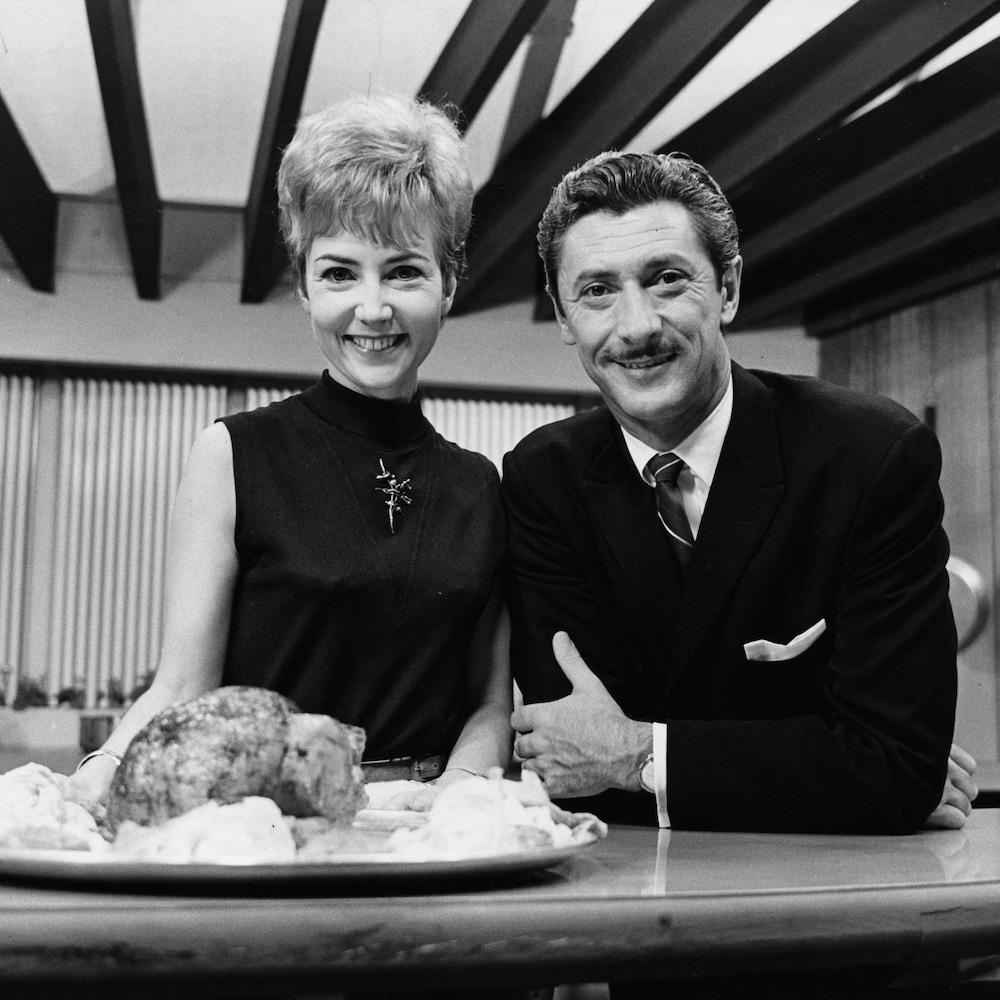 Dans un studio de télévision, les animateurs Lizette Gervais et Yoland Guérard sont debout, souriants, dans le décor d'une cuisine. Un plat de viande repose sur le comptoir devant eux et des casseroles sont accrochées sur le mur derrière.