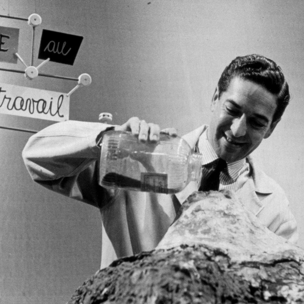 Fernand Seguin qui verse du sable sur une table pour former un volcan.