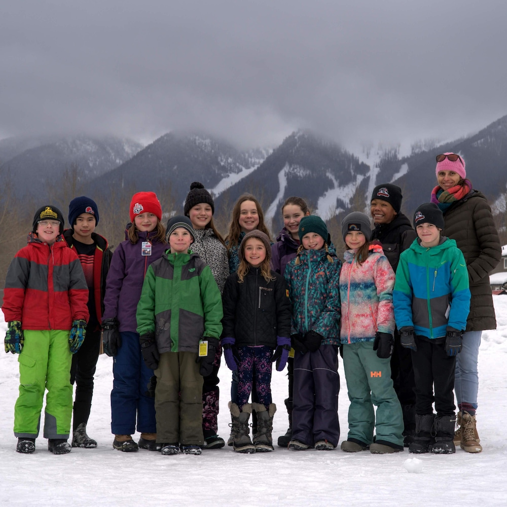 Une classe d'élèves de 9 à 11 ans pose à l'extérieur dans la neige avec des montagnes en arrière-plan.