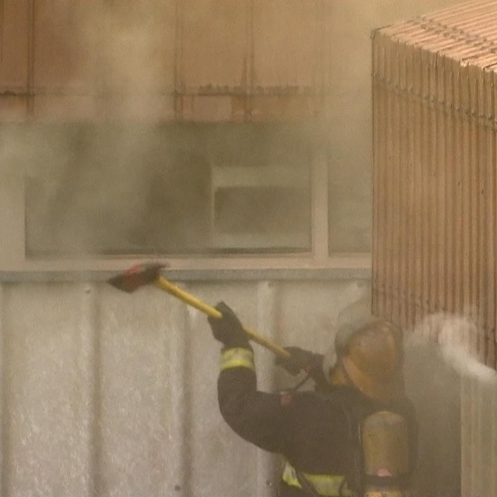 Un pompier casse un fenêtre
