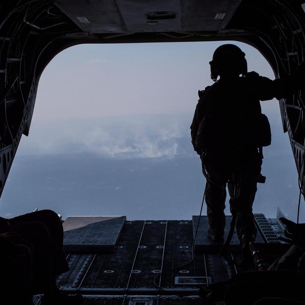 Un membre des Forces canadiennes observe un feu de forêt depuis l'arrière d'un hélicoptère Chinook.