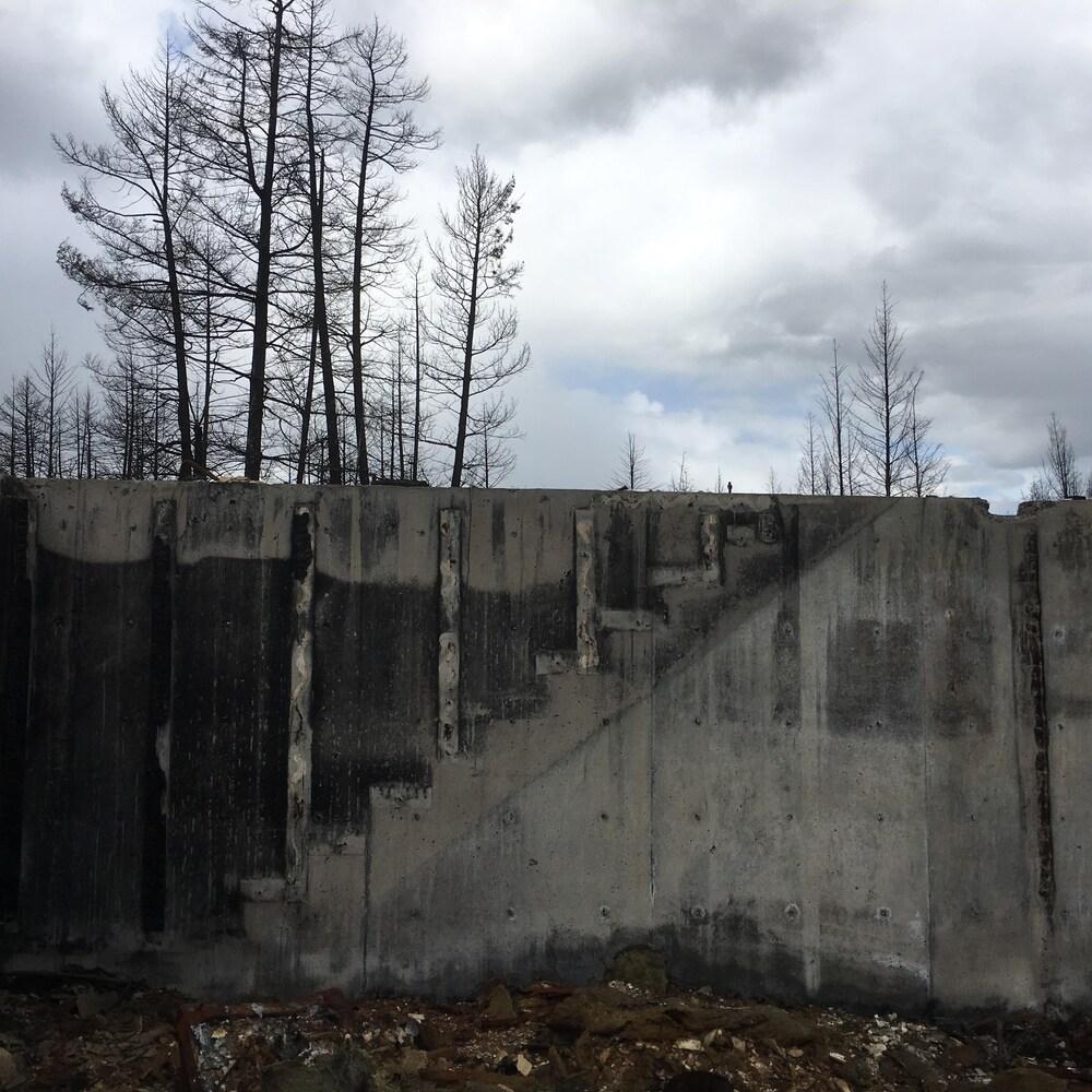 Restes de fondations de maison. Forme de l'escalier disparu imprimée par la suie sur le ciment de la fondation.