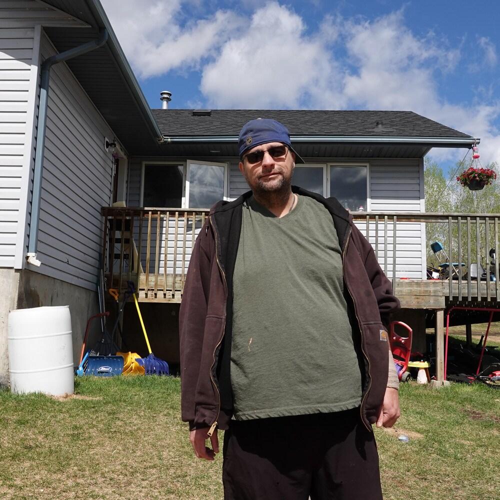 Mitchell Crevier devant une maison unifamiliale.