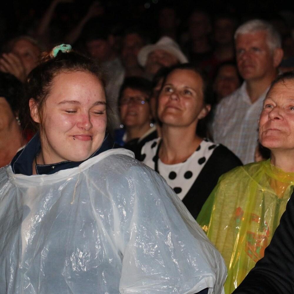 Femme les yeux fermés au sein de la foule.