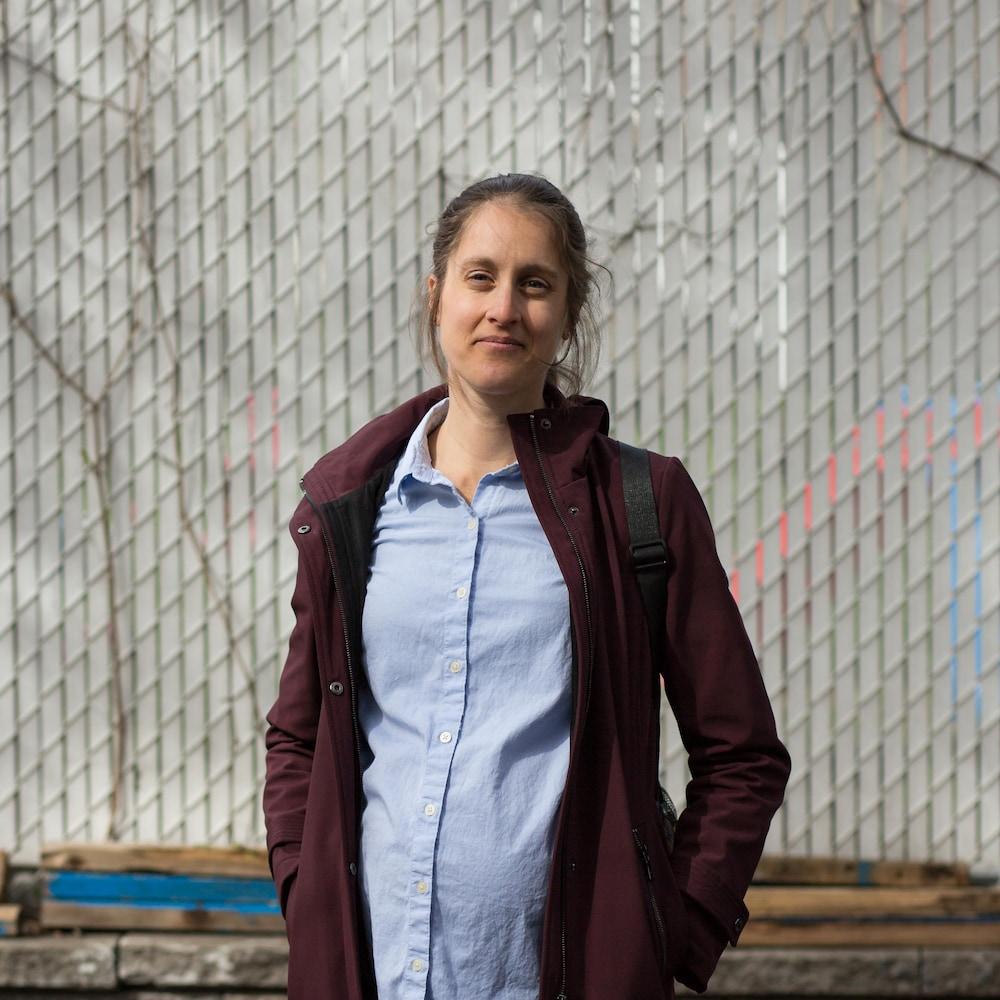 Emily Lavertu pose devant une clôture, dans un quartier de Montréal.