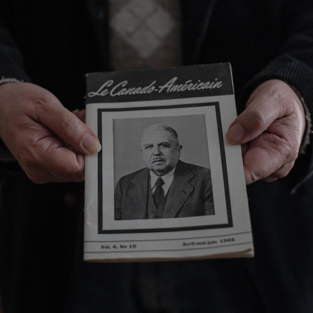 Robert Perreault tient un numéro du magazine « Le Canado-Américain » où figure un portrait de son grand-père Adolphe Robert.