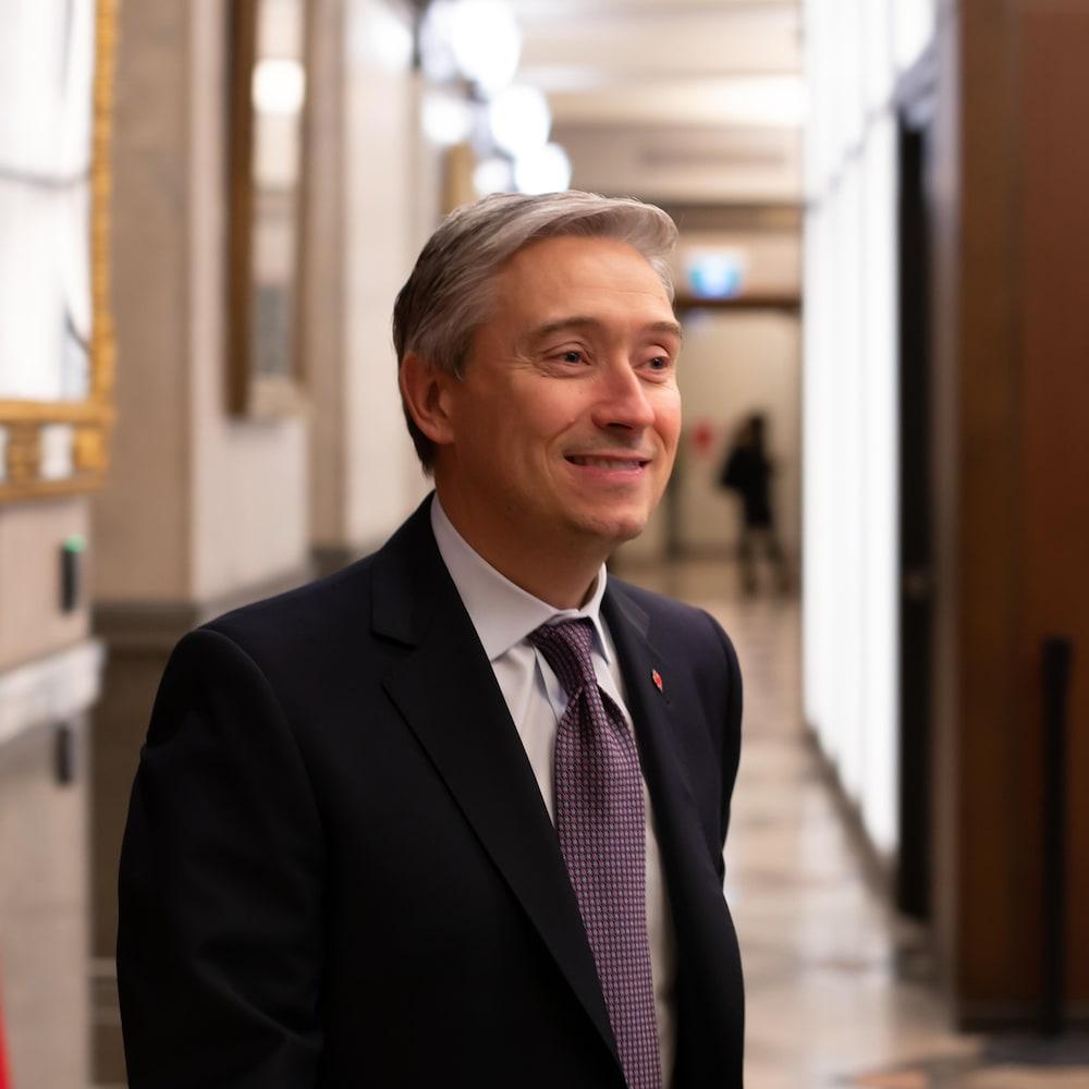 Le député dans un couloir, avec un drapeau canadien, à Ottawa.