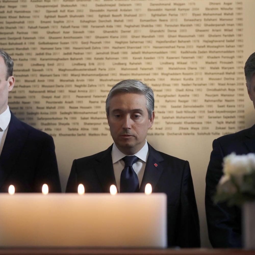 Les trois politiciens devant des chandelles durant une minute de silence au Haut–commissariat du Canada au Royaume–Uni, situé à Londres.