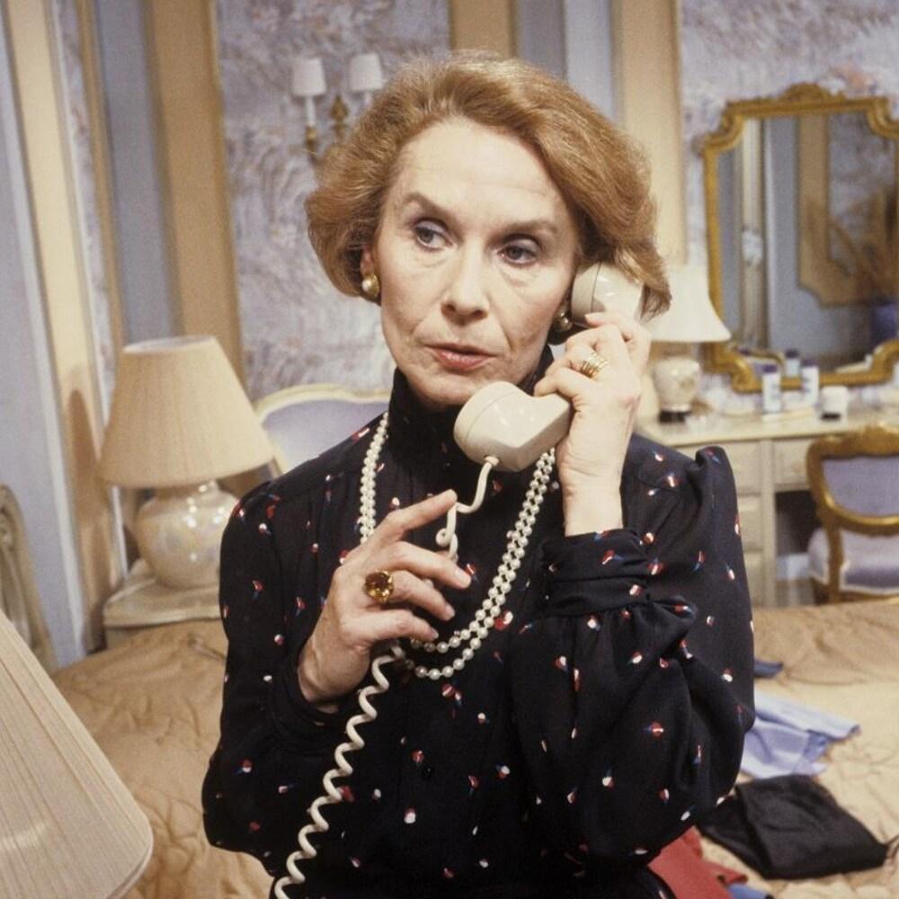 Dans une chambre à coucher, Arlette Montrachet (Françoise Faucher) est debout et elle parle au téléphone.