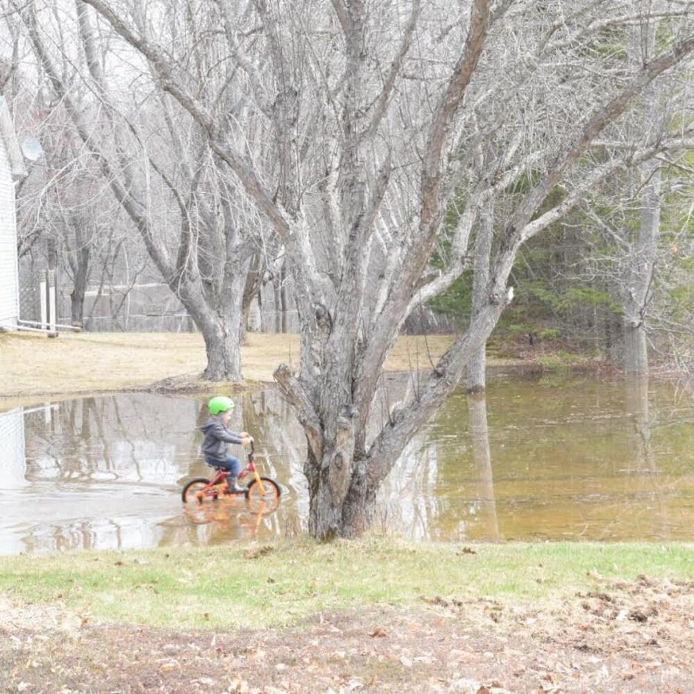 Un enfant fait du vélo sur un terrain inondé