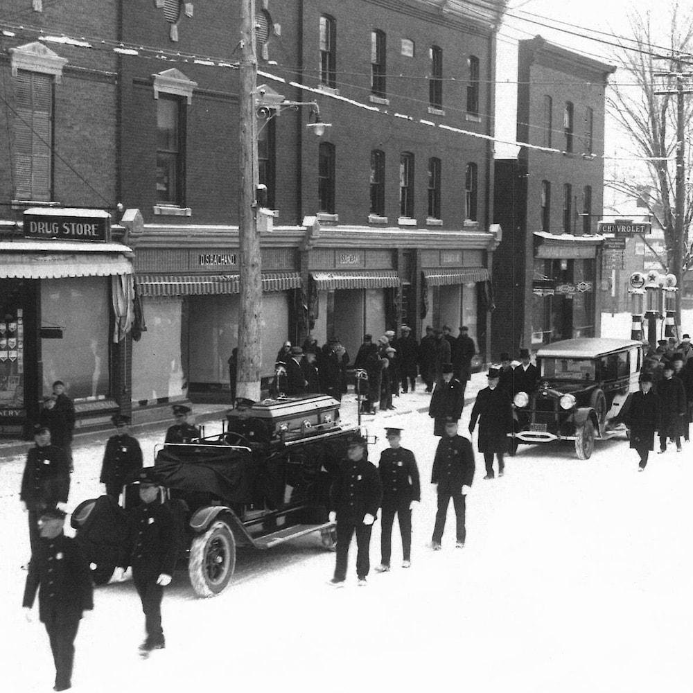 Une longue file de gens marche derrière les voitures du cortège funèbre du chef de police de Coaticook Johnny Boudreau.