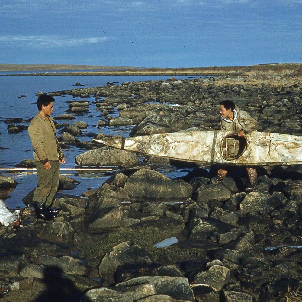 Deux hommes inuits, dont l'un porte un kayak, reviennent d'une chasse au caribou. La carcasse de l'animal repose sur les rochers qui forment la berge.