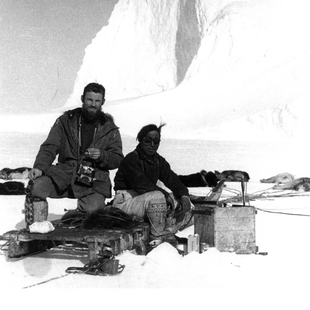 Deux hommes sur un traineau dans une photo en noir et blanc.