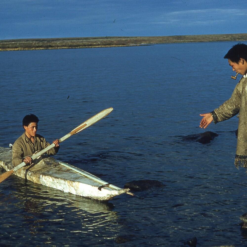 Deux Inuit tirent un caribou attaché à un kayak