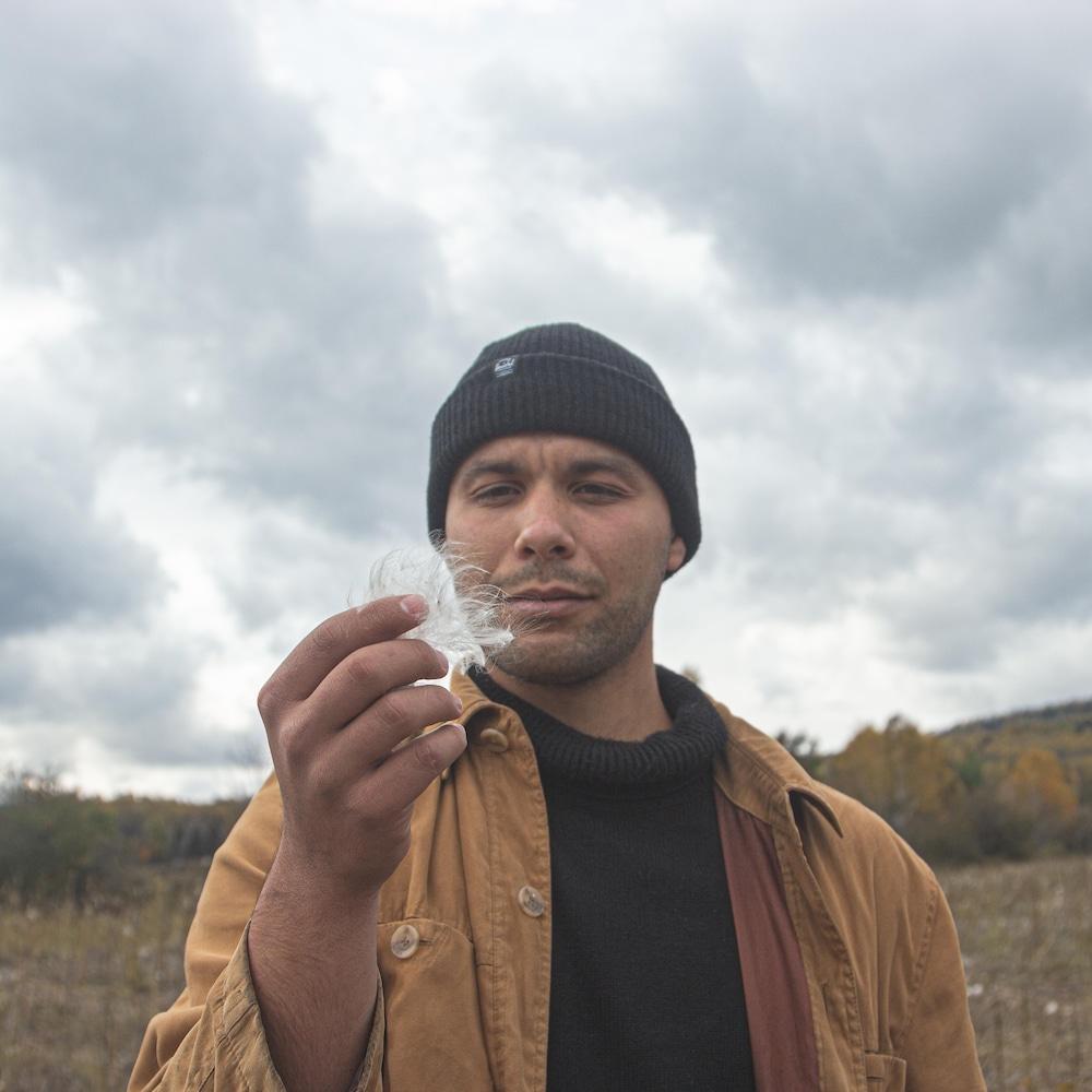 Gabriel Gouveia tient une fibre d'asclépiade dans ses mains et la regarde.