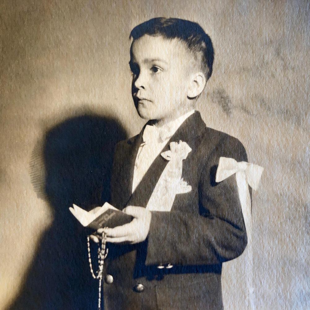Gaétan Larouche tient un livre et un chapelet.