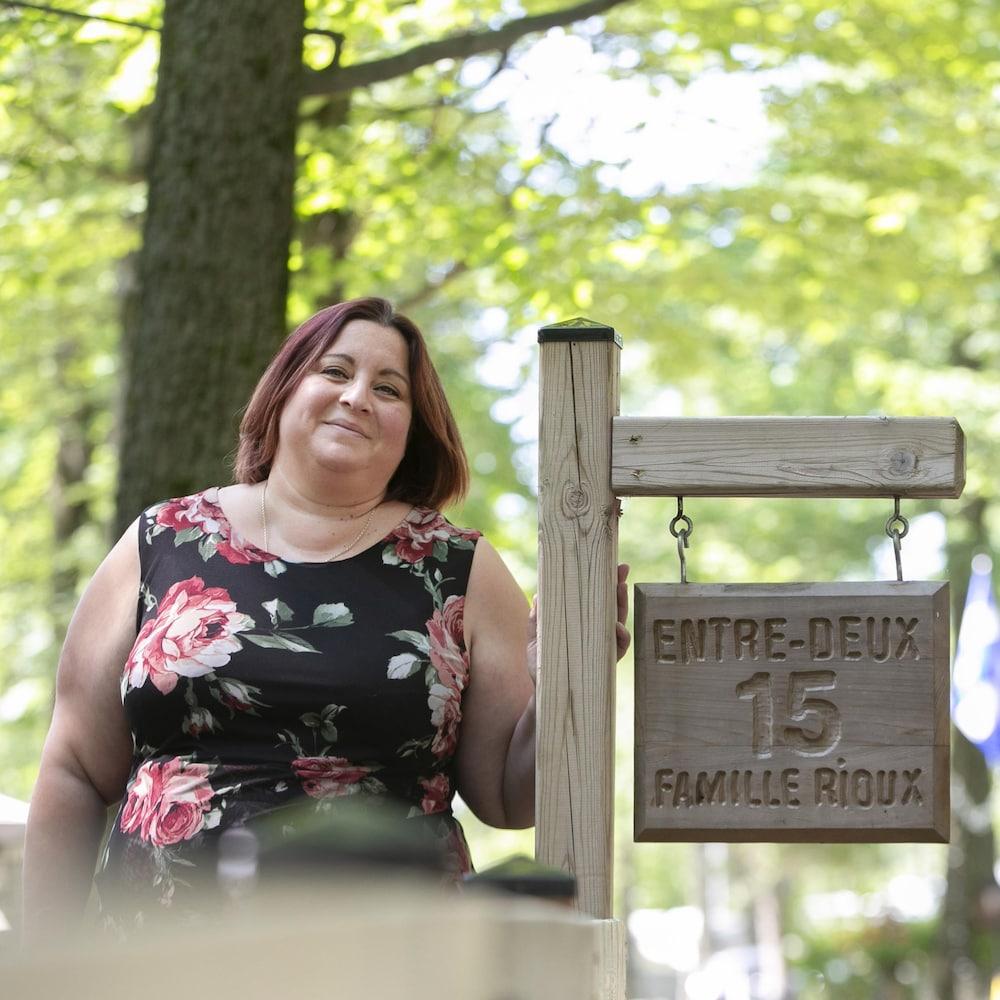 Une femme debout à l'extérieur et posant la main sur une plaque en bois sur laquelle il est gravé : Entre-deux, 15, Famille Rioux.