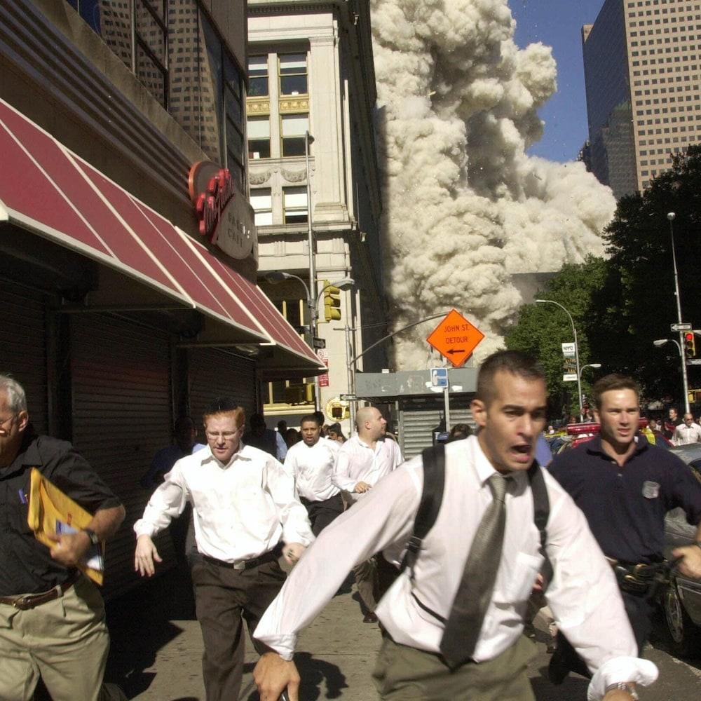 On voit des hommes le visage ébahi, de face, qui fuient dans une rue de Manhattan le nuage de poussière qui se trouve derrière eux.