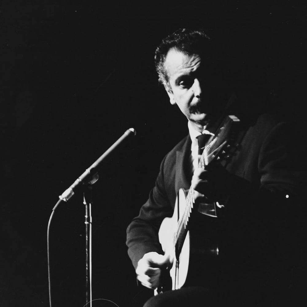 Le chanteur français Georges Brassens debout sur la scène en s'accompagnant à la guitare.