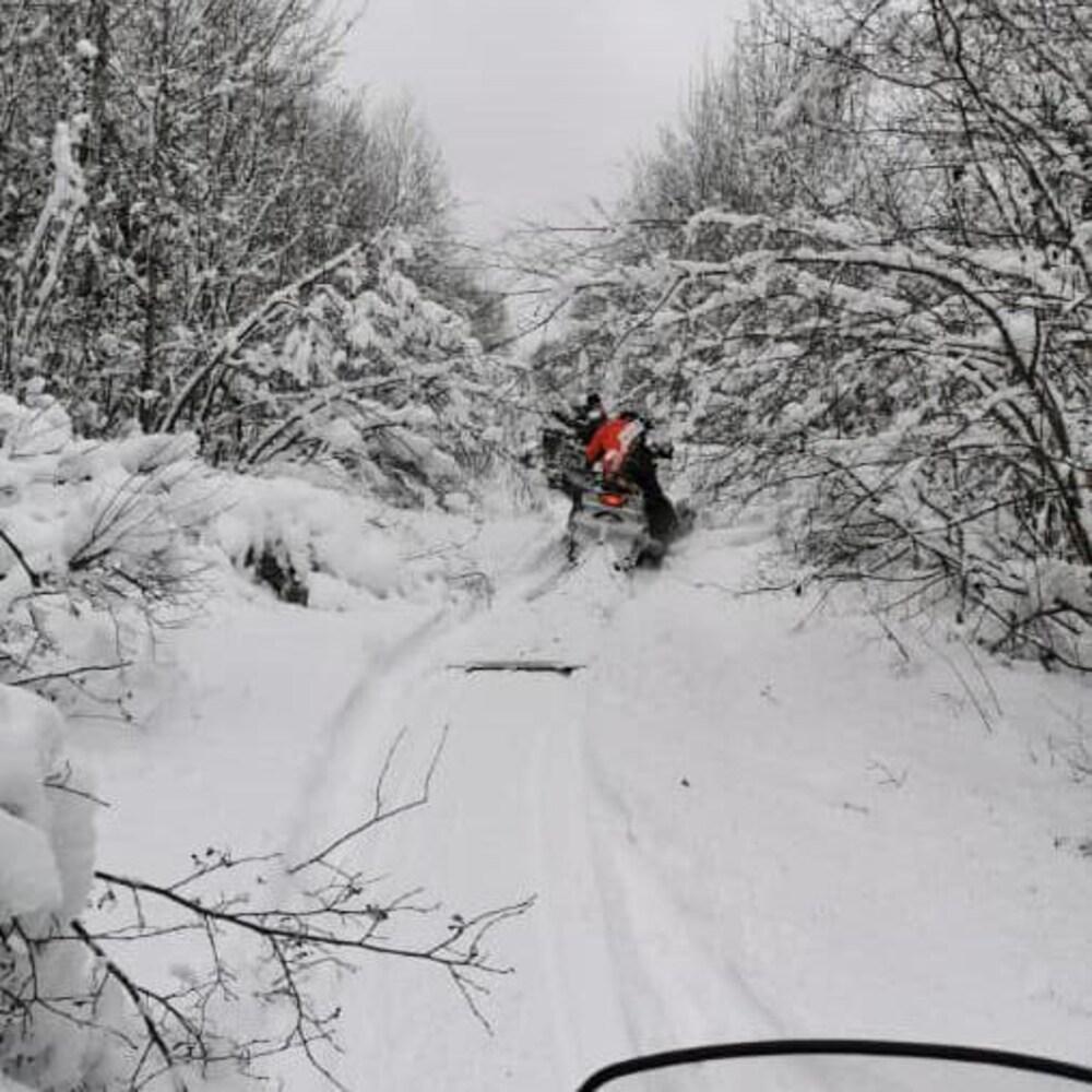 Un sentier de forêt enneigé avec des traces de motoneige et plus loin une personne sur une motoneige.