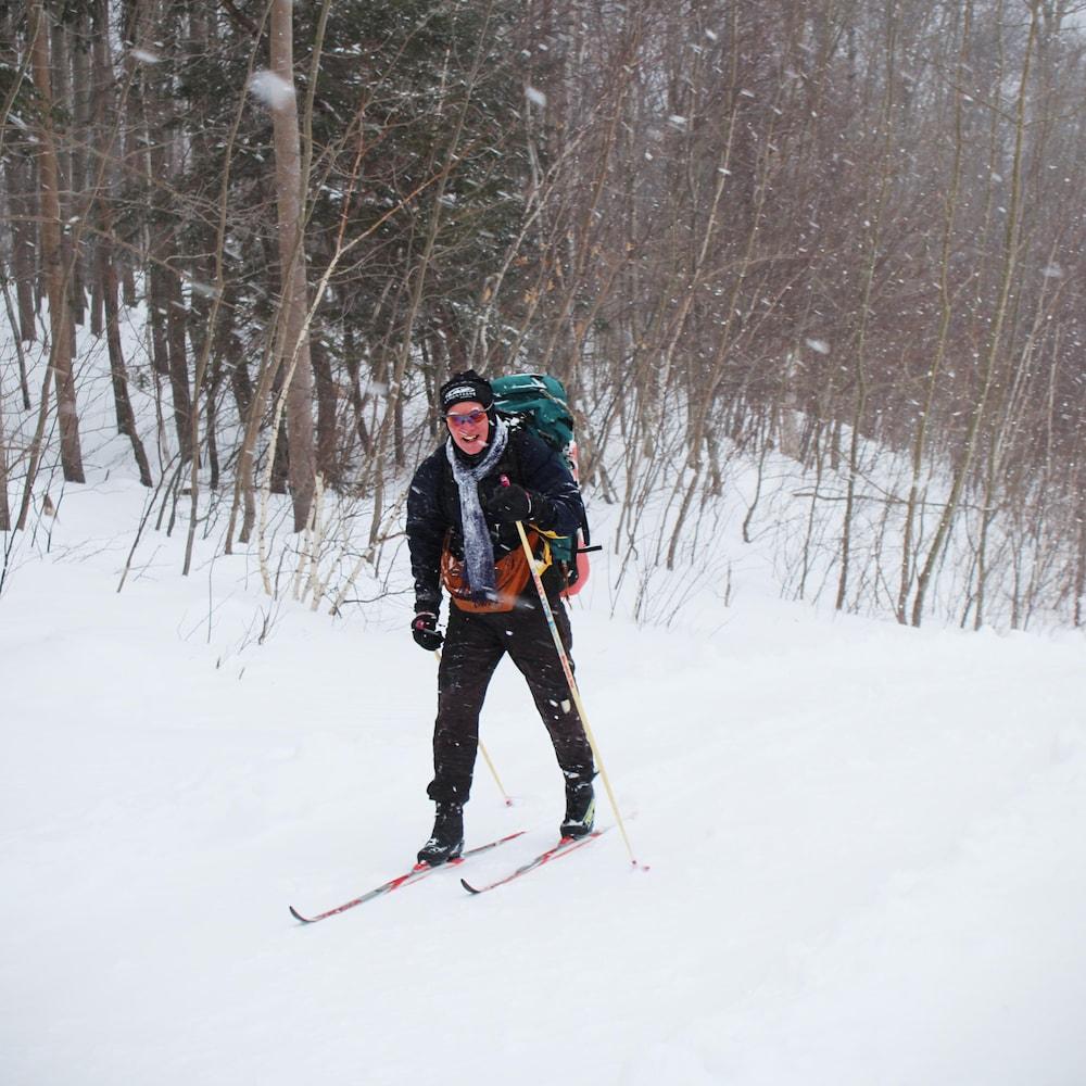 Gerry Fassett à l'entraînement, dans une tempête de neige, sac à dos sur les épaules et sourire au visage.