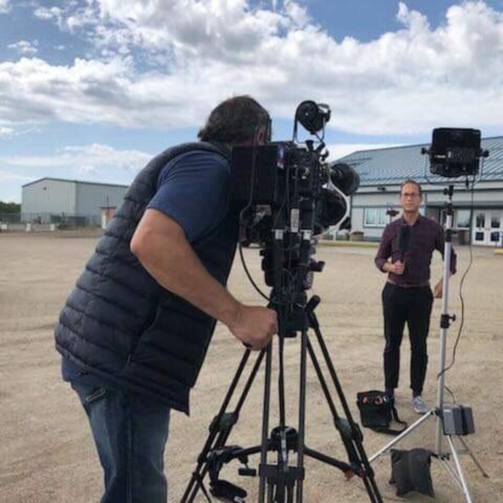 Un journaliste devant une caméra micro à la main
