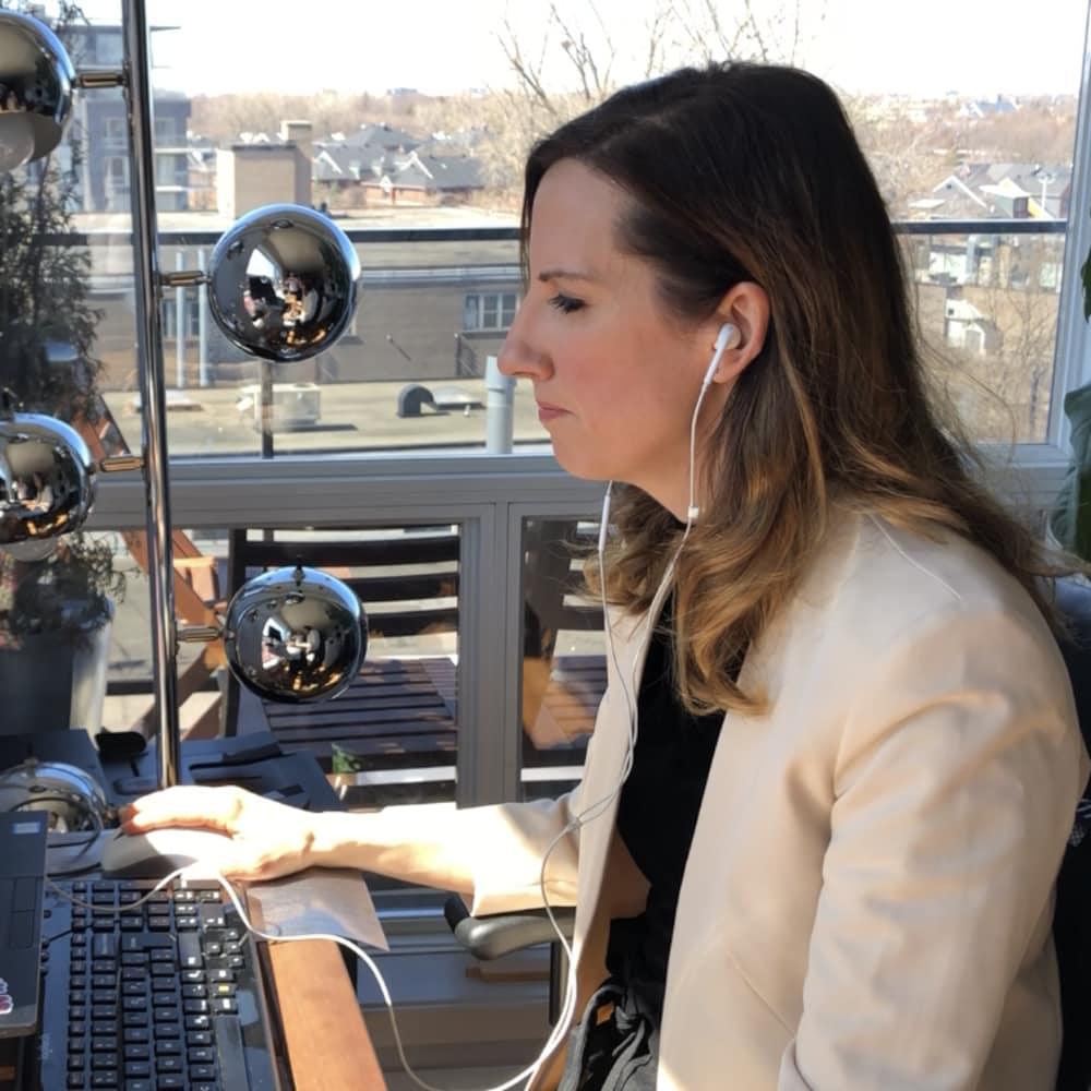 Julie Dufresne assise devant son ordinateur.