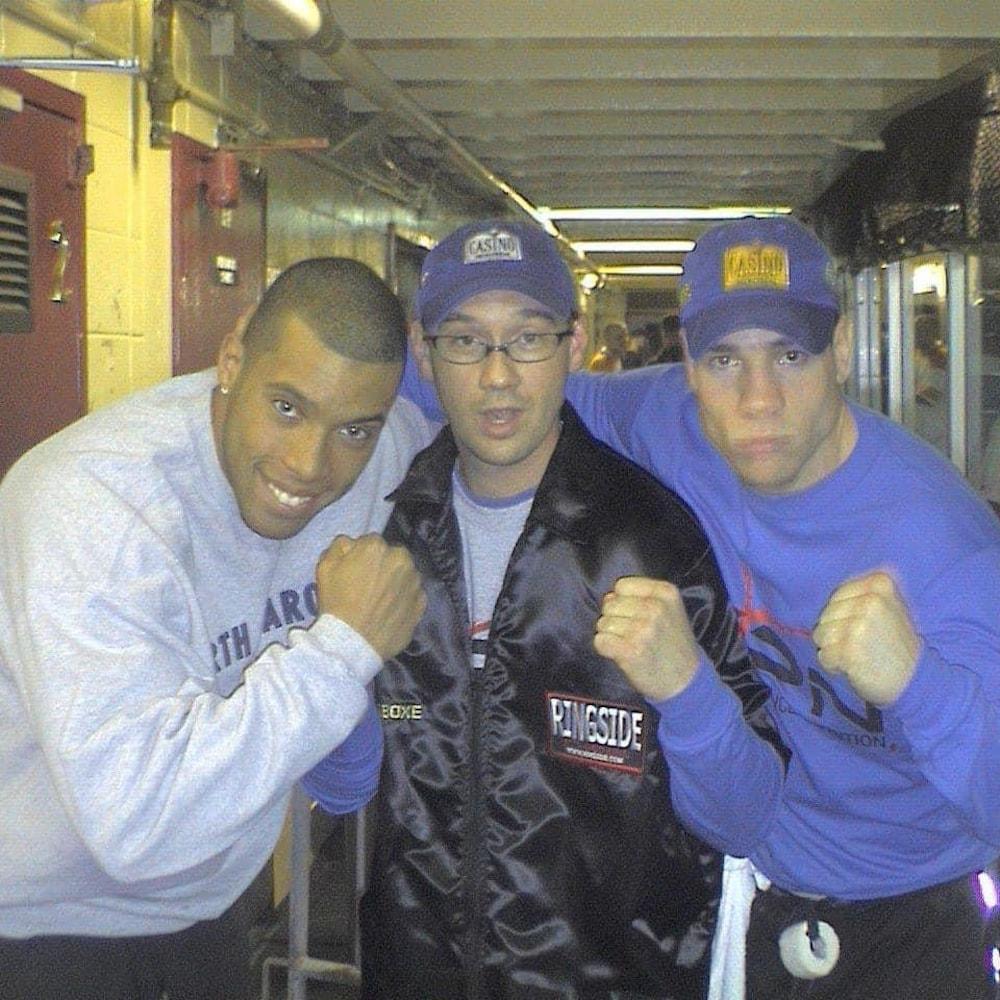 Photo de trois jeunes hommes, regardant la caméra et montrant leur poing. Ils sont vêtus de survêtements de sport.