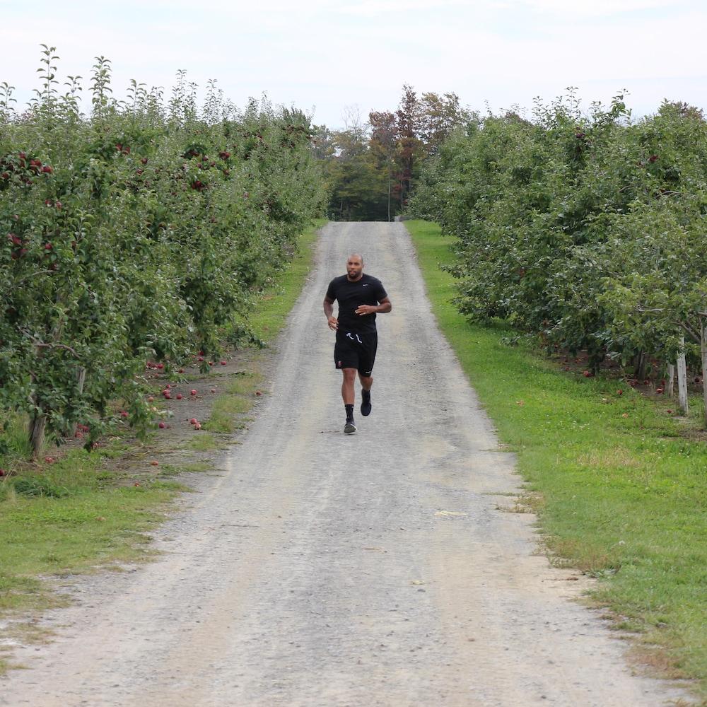 Éric Martel-Bohéli court sur un chemin de terre qui traverse un verger de l'île d'Orléans.