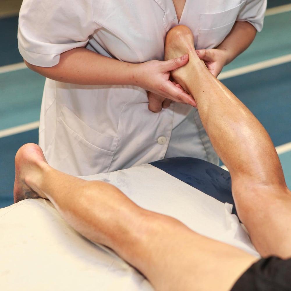 Une thérapeute masse le tendon d'Achille d'un patient, qui est couché sur le ventre sur une table de massage.