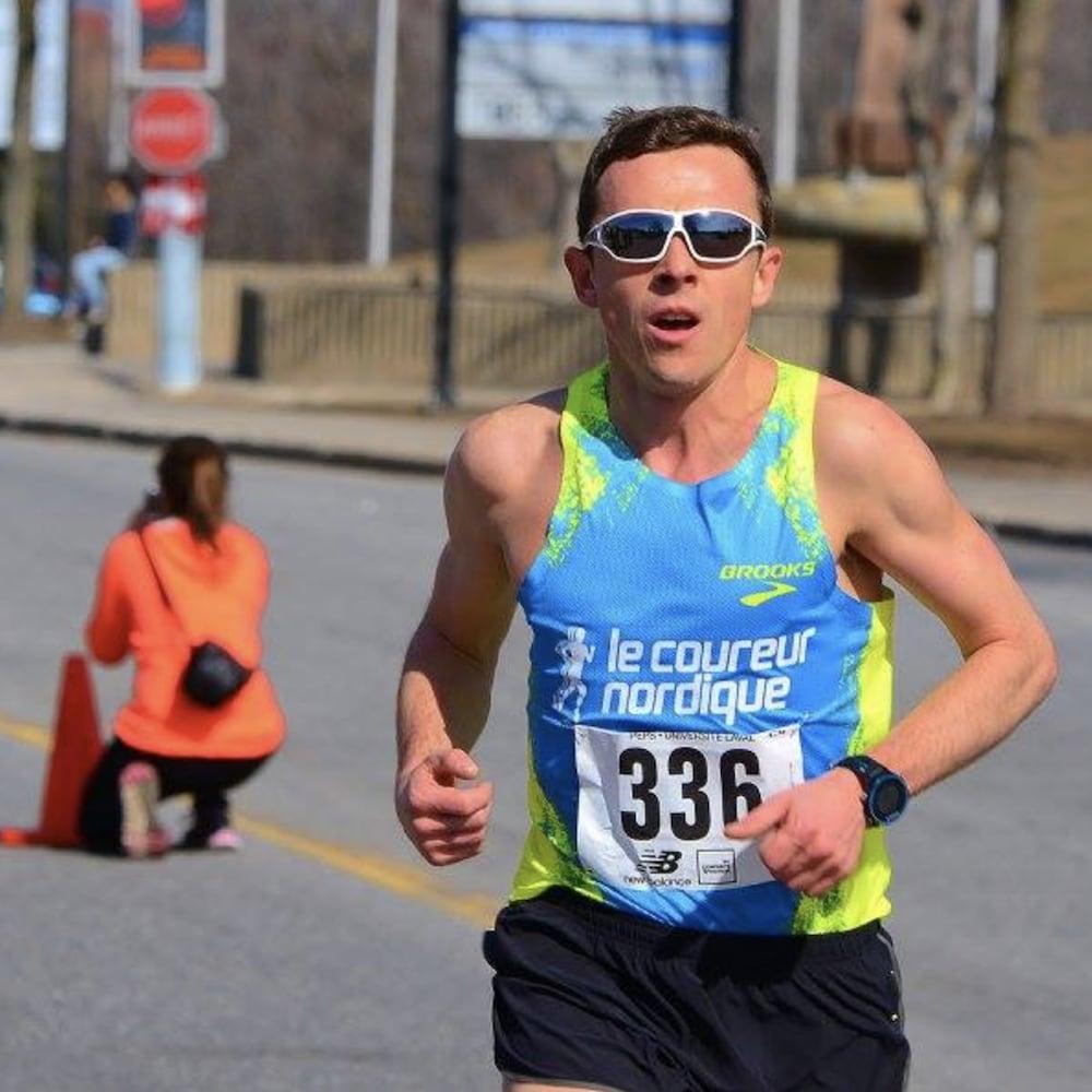 Jimmy Gobeil lors d'une épreuve de course à pied. Il porte des lunettes de soleil, une camisole verte et bleu ainsi qu'un dossard.