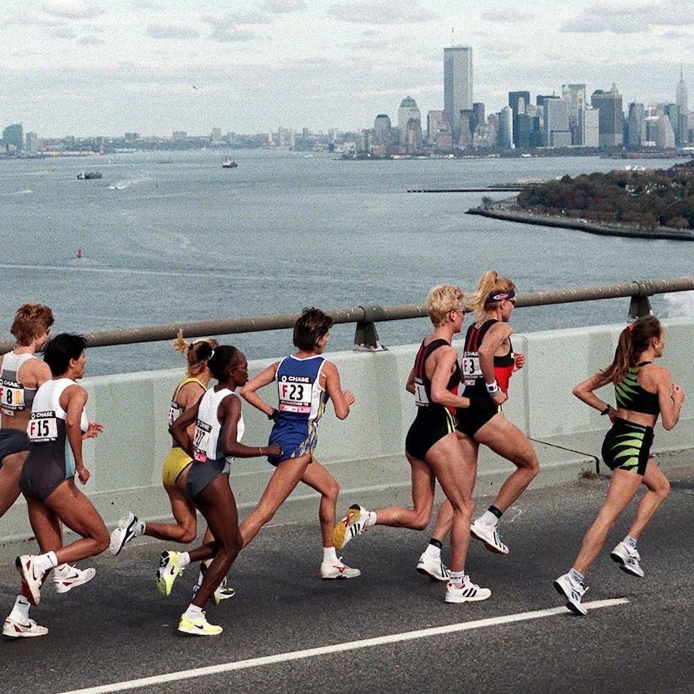 Un peloton de femmes courent sur un pont de la ville de New York, en 1998. En arrière-plan, les gratte-ciels de la ville.