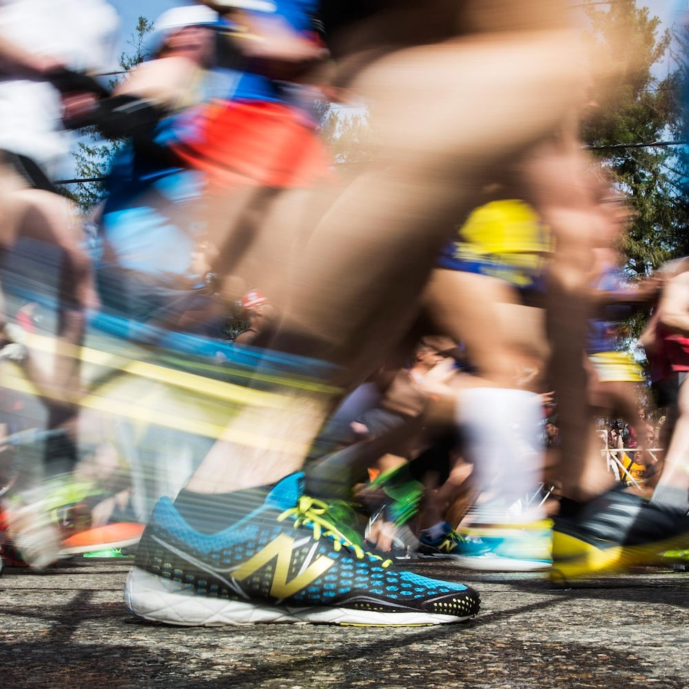 Focus sur un soulier de marque New Balance, en avant-plan. À l'arrière, les pas et les souliers de la foule de coureurs sont flous.