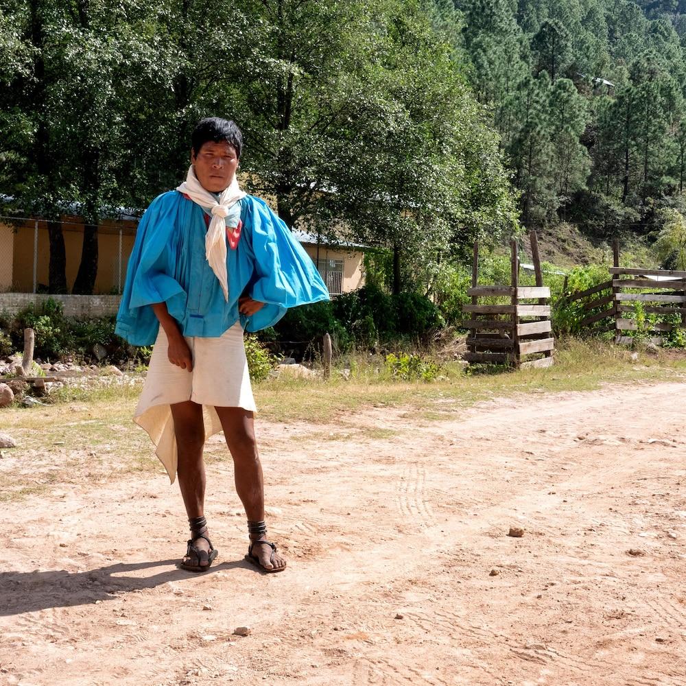 Un homme en habit traditionnel prend la pose : un chandail à manches amples, un foulard au cou, une jupette ainsi que des sandales.